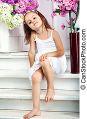 Little girl is sitting on the stairs