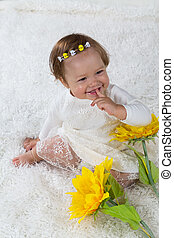 Little girl is sitting on the white carpet and laughs