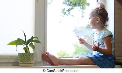 little girl is sitting on the window sill and waving hand to people