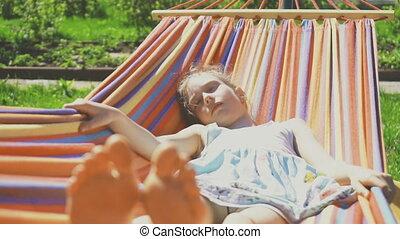 Little girl is sleeping in hammock on sunny day.