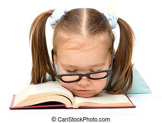 Little girl is sleeping on a book