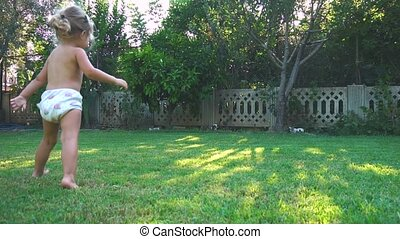 Little girl is spinning and running and falling on lawn at...