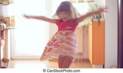 Little girl is spinning around inside the house