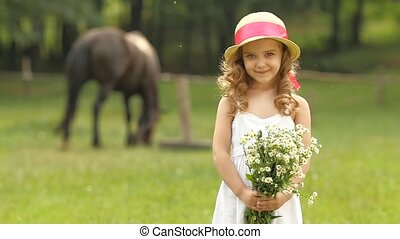 Little girl is standing in a park with a bouquet of wildflowers. Slow motion