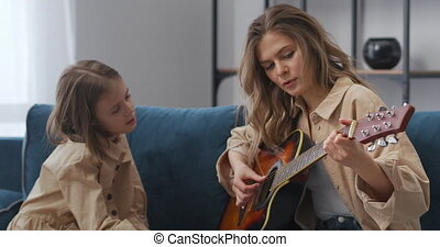 little girl is studying music, looking how her mother playing guitar at home, woman and her daughter are spending time together at weekend