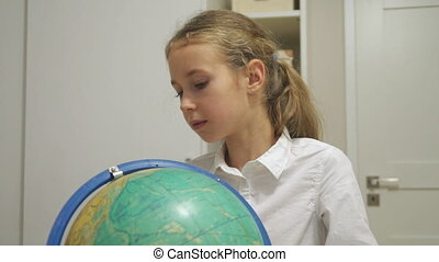 Little girl is studying the globe at home.