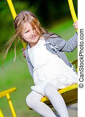 Little girl is swinging