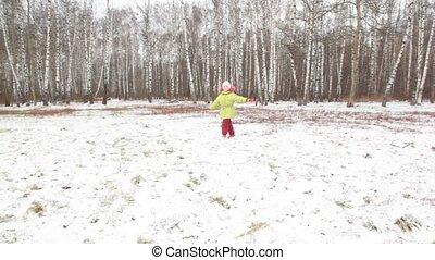 Little girl is turned in wood. - Little girl in green jacket...