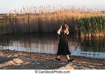 little girl is walking on the beach