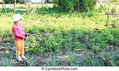 Little girl is watering garden and bed. Orchard irrigation....