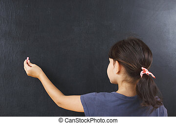 little girl is writing chalk on a blackboard