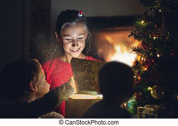 Little girl joyfully smiling as she opens golden gift box