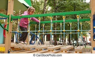 Little girl jump hang down steps on playground at sunny autumn day