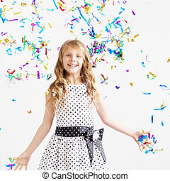 Happy excited laughing kid under sparkling confetti shower