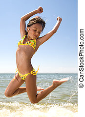 Little girl jumping at the sea - Little girl jumping high in...