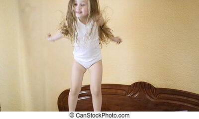 little girl jumping in bed
