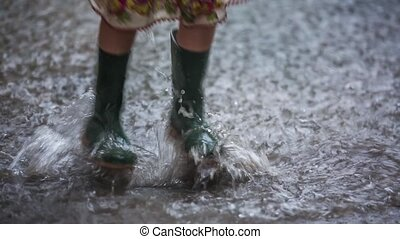 Little Girl Jumping In Huge Puddle