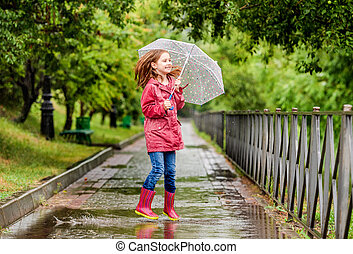 Little girl jumping in puddle