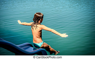 Little girl jumping in the water from a water slide