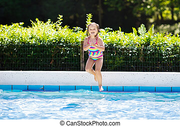 Little girl jumping into swimming pool - Happy little girl...