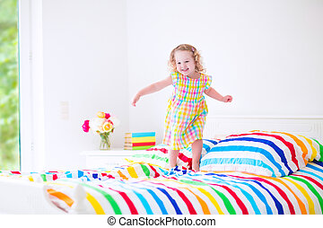 Little girl jumping on a bed - Cute little curly toddler ...