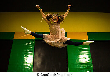 Little girl jumping on a trampoline and making twine split in play room for kids