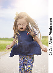 Little girl jumping on the road