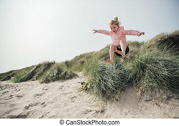 Little Girl Jumping Over a Sand Dune