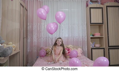 little girl jumping with balls