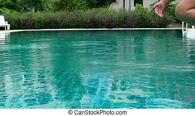 little girl jumps in a swimming pool. funy time in summer holiday