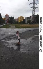 Little girl jumps in rubber boots in a puddle. - Little girl...
