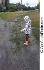 Little girl jumps in rubber boots in a puddle.