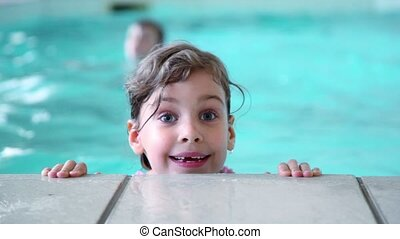 Little girl jumps in water near edge of pool, her brother at background