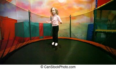 little girl jumps on trampoline in playroom. - Cute little...