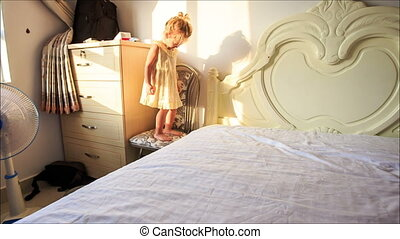 Little Girl Jumps up and down White Bed to Pillows on Floor