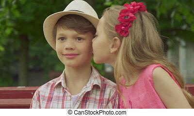 Little girl kisses boy's cheek on the bench