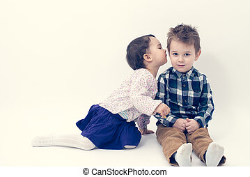 little girl kissing her older brother on the cheek isolated