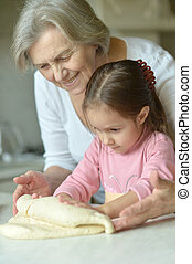 Little girl kneading dough with grandmother at the kitchen