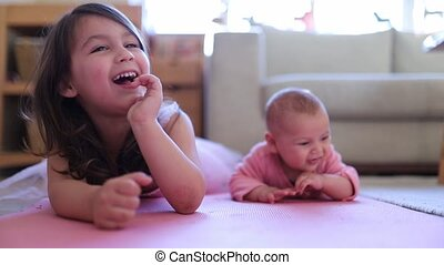 FHD Video of a little girl laughing with her baby sister while both are lying face down on a pink rug