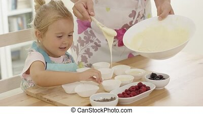 Little girl laughing as she helps with the baking