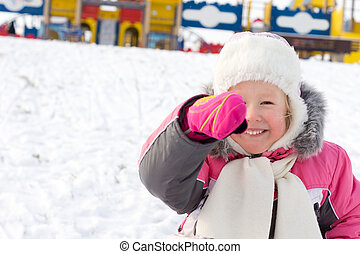 Little girl laughing in a snowy playground