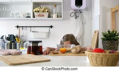 Little girl laughing on the kitchen with brewing teapot,...