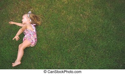 Little girl laying down at lawn and having fun at backyard