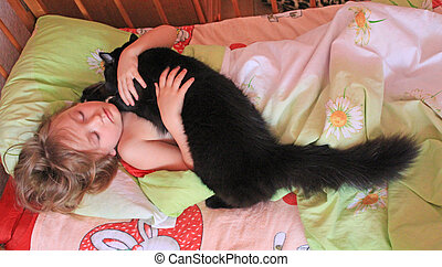Little girl laying in bed together with her cat. Together with your pet