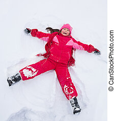 Little girl laying in star shape in snow - Happy girl in red...