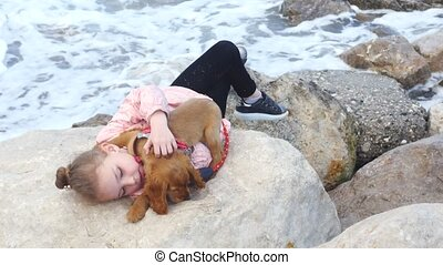 Little girl laying on the rocks with her sweet puppy