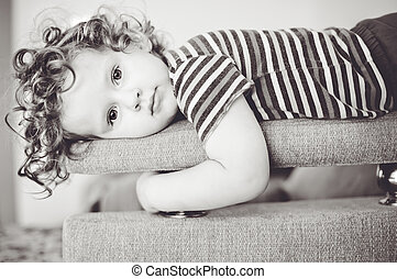 Little girl lays on a sofa. Looking into the camera.