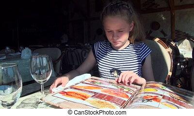 Little girl leafing through menu - Little girl leafing...