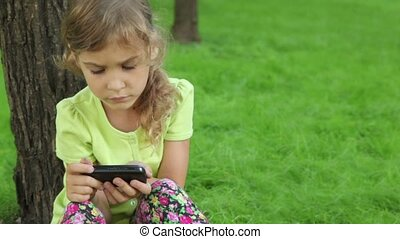 Little girl leans against tree at grass and watch on cell phone display