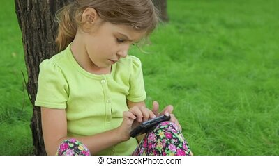 Little girl leans on grass and plays with cell phone